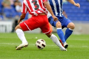 Two footballers challenging for a ball